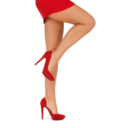 people, fashion and footwear concept - close up of woman legs in red high heeled shoes