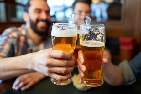 Люди, мужчины, отдых, дружба и празднование концепции - счастливые друзья-мужчины пить пиво и звон бокалов в баре или пабе