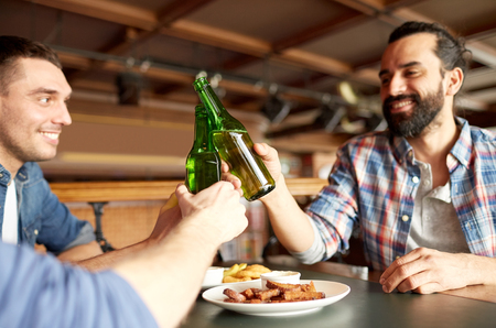 clinking: people, men, leisure, friendship and celebration concept - happy male friends drinking beer and clinking bottles at bar or pub