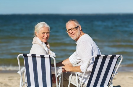 folding chair: family, age, travel, tourism and people concept - happy senior couple sitting on deck chairs on summer beach
