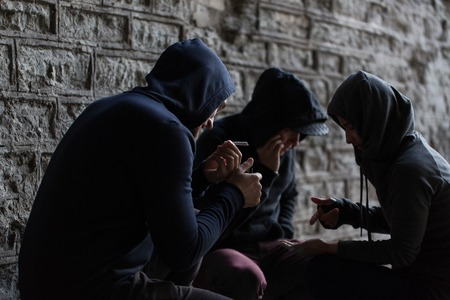 pernicious habit: substance abuse, addiction and bad habits concept - close up of young people smoking cigarettes outdoors Stock Photo