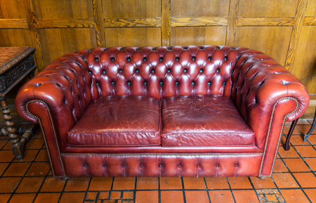 comfort room: comfort, antique furniture and interior concept - close up of vintage leather sofa