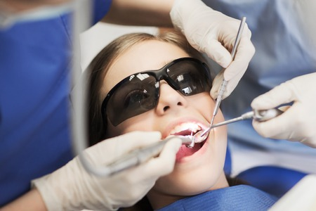treating: people, medicine, stomatology and health care concept - female dentists with mirror, drill and probe treating patient girl teeth at dental clinic office