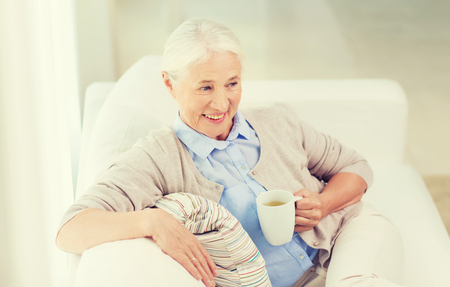 green couch: age, drink and people concept - happy smiling senior woman with cup of tea at home