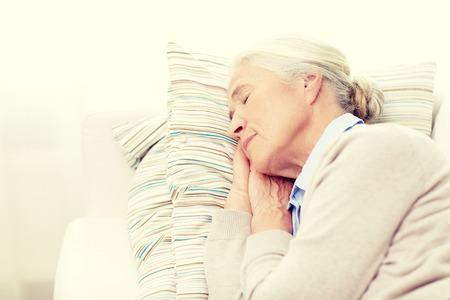 la edad, la gente se relaje y concepto - mujer mayor feliz duerme en la almohadilla en el hogar Foto de archivo