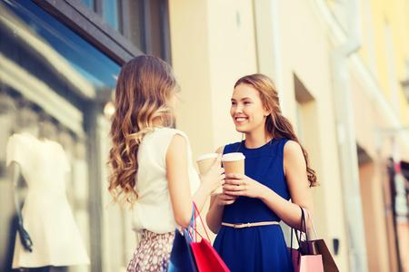 vendita, il consumismo e la gente concetto - giovani donne felici con borse della spesa e bicchieri di carta caffè parlando al vetrina in città