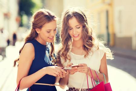 conceito de venda, consumismo e pessoas - mulheres jovens felizes com sacolas de compras e smartphone na rua da cidade Imagens