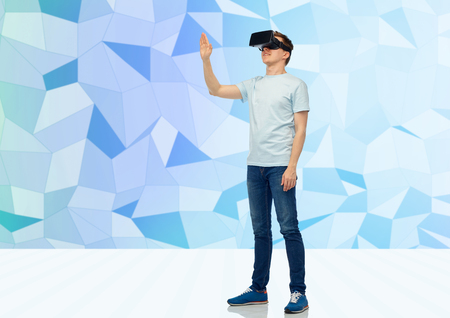 game over: 3d technology, virtual reality, entertainment, cyberspace and people concept - happy young man with virtual reality headset or 3d glasses playing game and touching something over low poly background Stock Photo