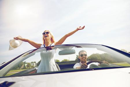 Viaje por carretera, viajes, citas, una pareja y concepto de la gente - hombre feliz y mujer que conduce en coche descapotable al aire libre