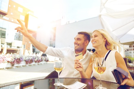 date, people, payment and finances concept - happy couple with wallet, credit card and wine glasses calling waiter for bill payment at restaurant Stock Photo