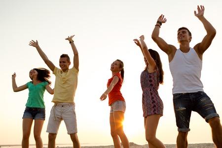 concepto de amistad, vacaciones de verano, días de fiesta, fiesta y la gente - grupo de amigos sonriendo bailando en la playa