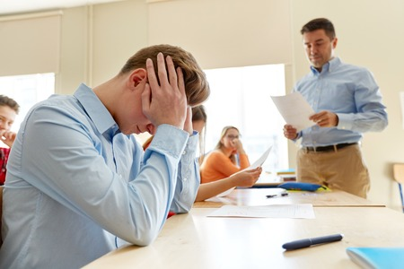 education, high school, learning and people concept - upset student boy and teacher with bad test results in classroom