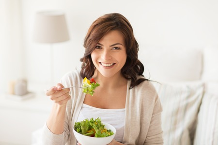 eating salad: healthy eating, dieting and people concept - smiling young woman eating vegetable salad at home