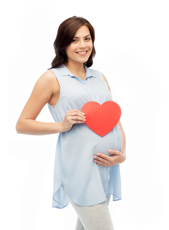 pregnancy, love, people and expectation concept - happy pregnant woman with red heart shape touching her belly over white background Stock Photo