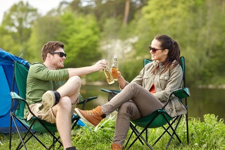 campsite: camping, travel, tourism, hike and people concept - happy couple clinking beer bottles at campsite tent Stock Photo