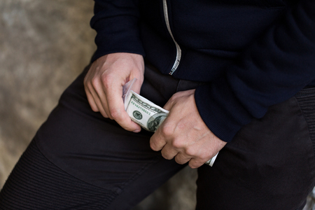 drug trafficking: drug trafficking, crime, addiction, people and sale concept - close up of addict or dealer hands with dollar money and dose Stock Photo