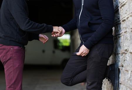 Drogenhandel, Kriminalität, Sucht und Verkauf Konzept - Nahaufnahme von Süchtigen Kauf Dosis von Drogenhändler auf der Straße