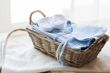 babyhood: clothing, babyhood, motherhood and object concept - close up of white baby bootees with pile of clothes and towel for newborn boy in basket on table Stock Photo