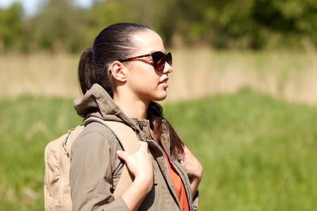 Reizen, wandelen, backpacken, toerisme en mensen concept - gelukkige jonge vrouw in zonnebril met rugzak wandelen langs landweg buitenshuis