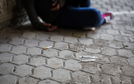 youth crime: substance abuse, addiction, people and drug use concept - close up of addict woman and used syringes on ground Stock Photo
