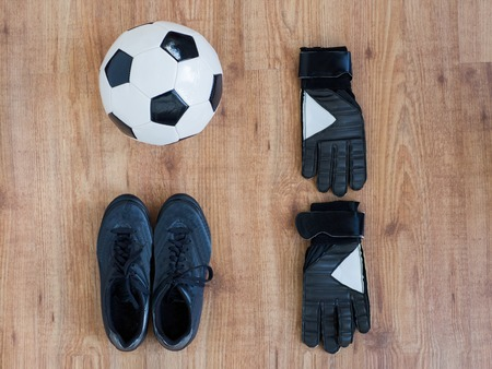 soccer boots: sport, soccer, football and sports equipment concept - close up of ball, boots and goalkeeper gloves on wooden background
