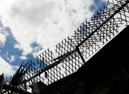imprisonment: imprisonment concept - close up of fence with barbed wire and mesh in prison Stock Photo