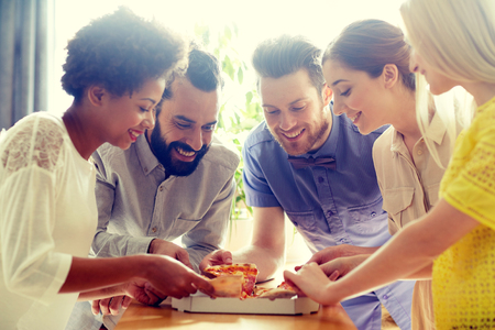 people eating: business, food, lunch and people concept - happy business team or friends eating pizza in office