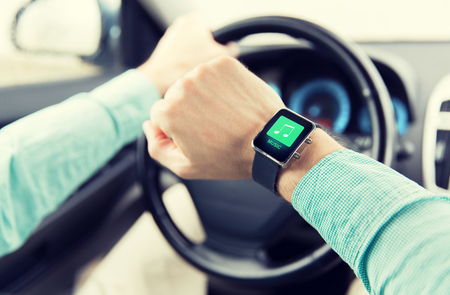 close icon: transport, business trip, technology, time and people concept - close up of man with music icon on smart watch driving car