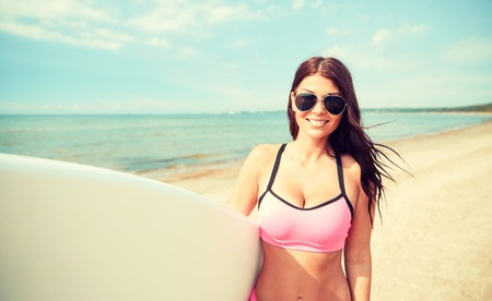 summer vacation, travel, surfing, water sport and people concept - young woman in swimsuit with surfboard on beach Stock Photo