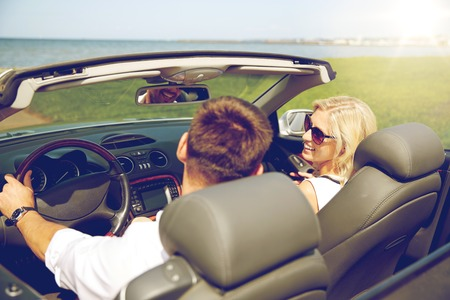 couple dating: leisure, road trip, dating, couple and people concept - happy man and woman driving in cabriolet car outdoors