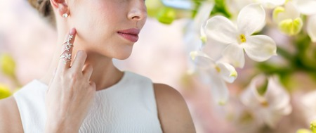 glamour luxury: glamour, beauty, jewelry and luxury concept - close up of beautiful woman with golden ring and diamond earring over natural lilac blossom background