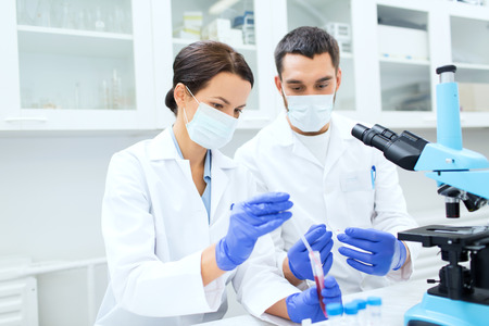scientists: science,  technology, biology and people concept - young scientists with pipette, test tube and microscope making research in clinical laboratory