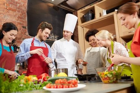 cooking class, culinary, food and people concept - happy group of friends and male chef cook cooking in kitchen photo
