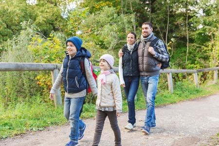 冒険、旅行、観光、ハイキング、人々 の概念 - 幸せな家族と歩いて森の中でバックパックします。