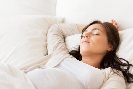 durmiendo: el embarazo, el descanso, la gente y el concepto de expectativa - mujer embarazada feliz que duerme en cama en su casa Foto de archivo