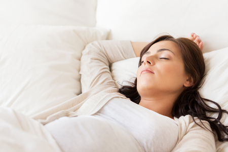 sleeping rooms: pregnancy, rest, people and expectation concept - happy pregnant woman sleeping in bed at home