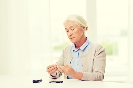 blood sugar level: medicine, age, diabetes, health care and people concept - senior woman with glucometer checking blood sugar level at home