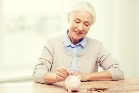 savings, money, annuity insurance, retirement and people concept - smiling senior woman putting coins into piggy bank at home Stock Photo