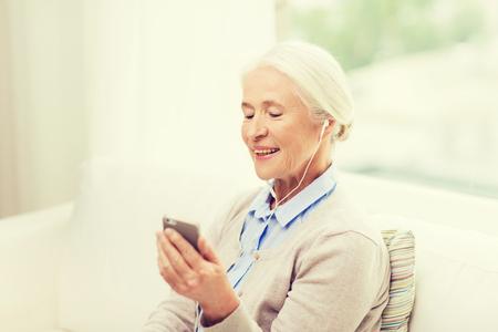 listening to music: la tecnología, la edad y las personas concepto - mujer mayor feliz con el teléfono inteligente y auriculares escuchando música en casa Foto de archivo