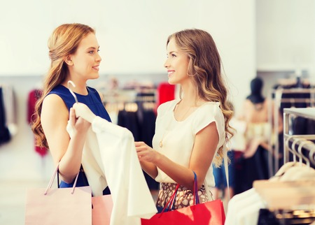 choosing clothes: sale, consumerism and people concept - happy young women with shopping bags choosing clothes at clothing shop Stock Photo