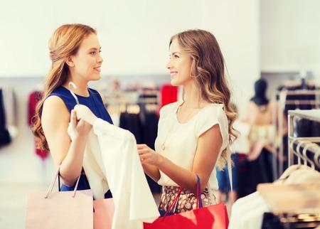 Verkauf, Konsum und Menschen Konzept - glückliche junge Frauen mit Einkaufstaschen Kleidung in Bekleidungsgeschäft Wahl