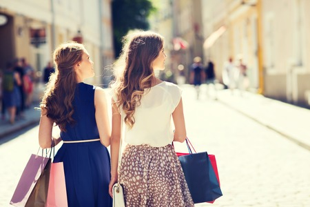 consumerism: sale, consumerism and people concept - happy young women with shopping bags walking along city street