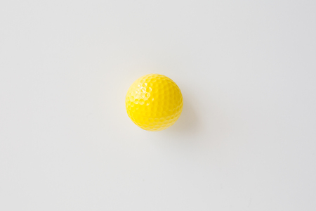 objects equipment: sport, fitness, game, sports equipment and objects concept - close up of yellow golf ball over white background from top Stock Photo