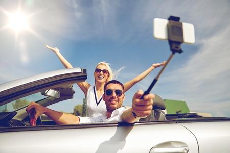 road trip, reizen, paar, technologie en mensen concept - gelukkig man en vrouw rijden in cabriolet auto en het nemen van foto met smartphone op selfie stok