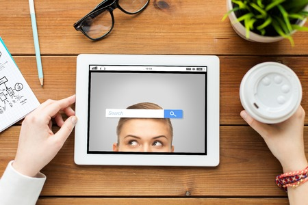 internet browser: business, education, technology, people and internet concept - close up of woman with internet browser search bar on tablet pc computer screen and coffee on wooden table