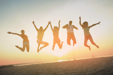 friendship, summer vacation, holidays, party and people concept - group of smiling friends dancing and jumping on beach Stock Photo