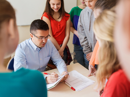 education, school, learning, teaching and people concept - group of students and teacher checking tests at school Stock Photo