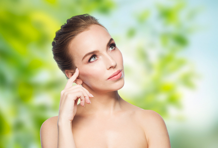 beautiful background: beauty, people, eco and health concept - beautiful young woman touching her face over green natural background