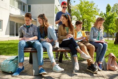 la educación, la escuela secundaria y la gente concepto - grupo de estudiantes adolescentes felices con los cuadernos de aprendizaje en el patio del campus