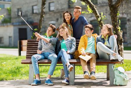 教育、高校、技術と人の概念 - 幸せな 10 代の学生やスマート フォンと一脚で selfie を取って友人のグループ